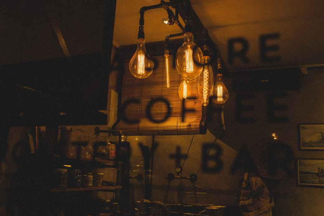 cafe with different bulbs behind window with cafe information