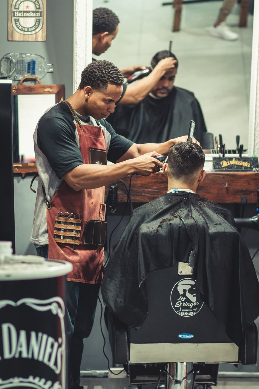 person cutting hair of man